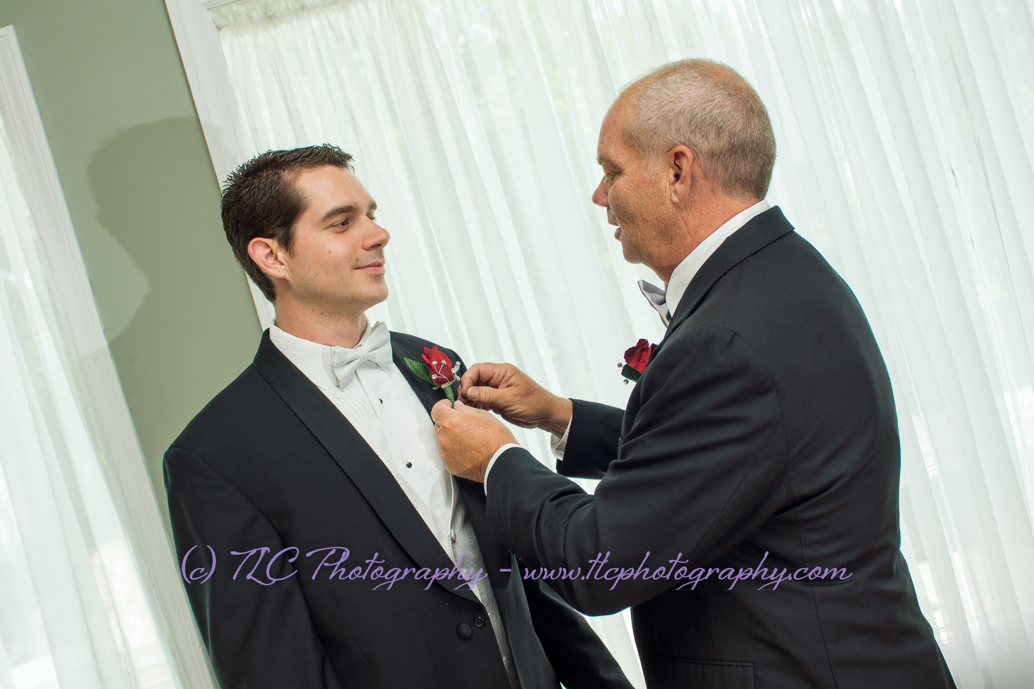 Dad helping the groom with his boutonniere before the wedding ceremony