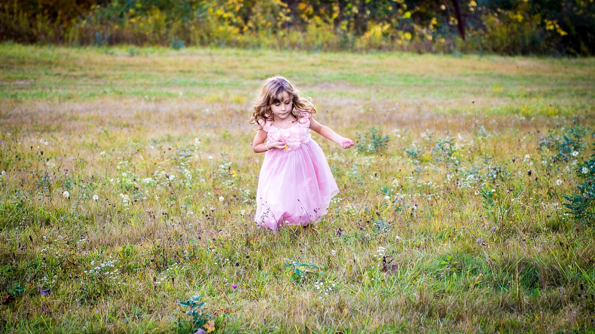 Little girl running through the grass.  By TLC Photography